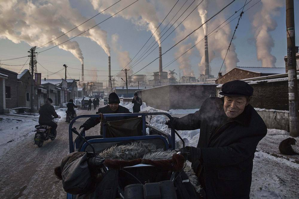 Canadian photographer Kevin Frayer, for Getty Images, 1st prize singles in the Daily Life category. The picture shows Chinese men pulling a tricycle in a neighborhood next to a coal-fired power plant in Shanxi, China, on 26 November 2015