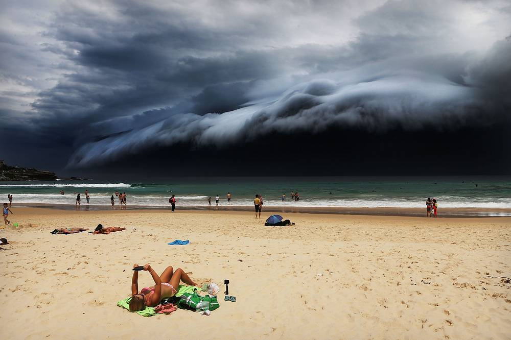 Australian photographer Rohan Kelly, Daily Telegraph, 1st prize singles in the Nature category. The picture shows a massive 'cloud tsunami' looming over Sydney as a sunbather reads, oblivious to the approaching cloud on Bondi Beach, Sydney, Australia on 06 November 2015