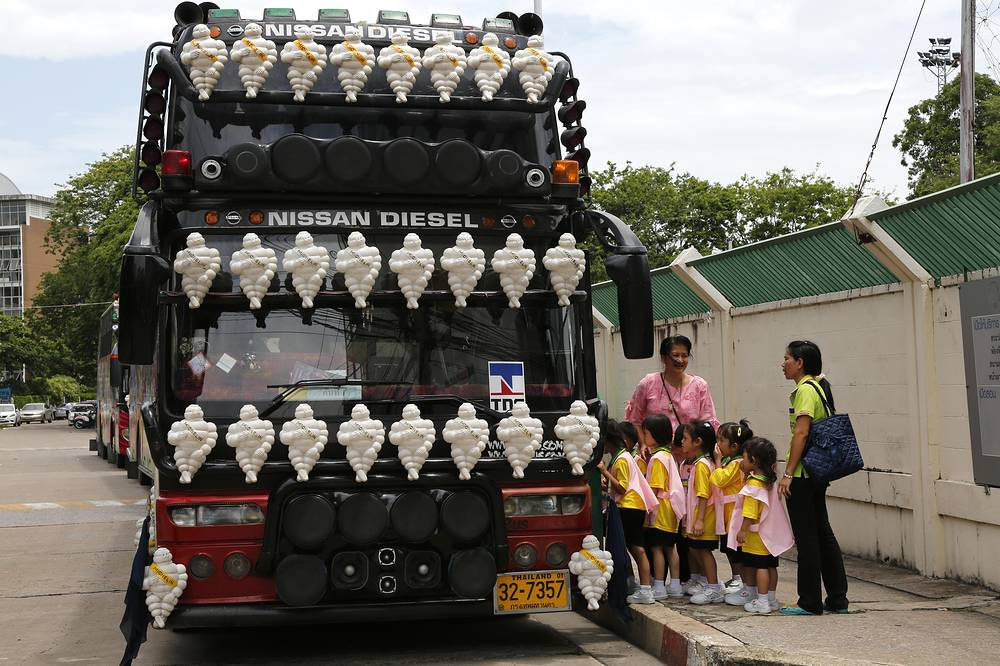 Young Thai school children board a decorated bus after a school excursion, in Bangkok, Thailand