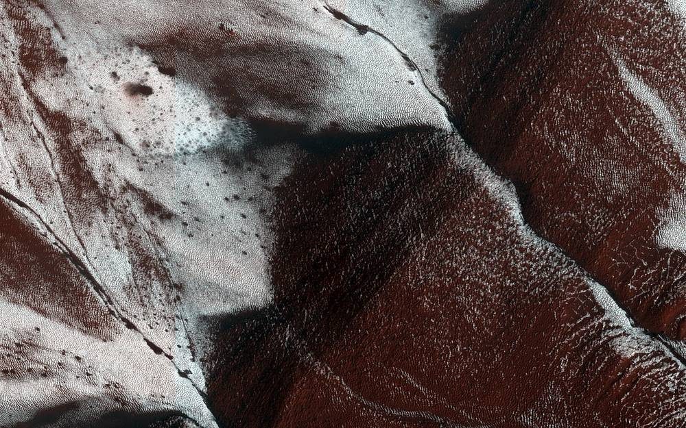 Mars Reconnaissance Orbiter (MRO), a multipurpose spacecraft designed to conduct reconnaissance and exploration of Mars from orbit was launched August 12, 2005 and is still operational. Photo: An area on the surface of Mars, displaying frosted gullies on a south-facing slope within a crater, was made by MRO in 2014