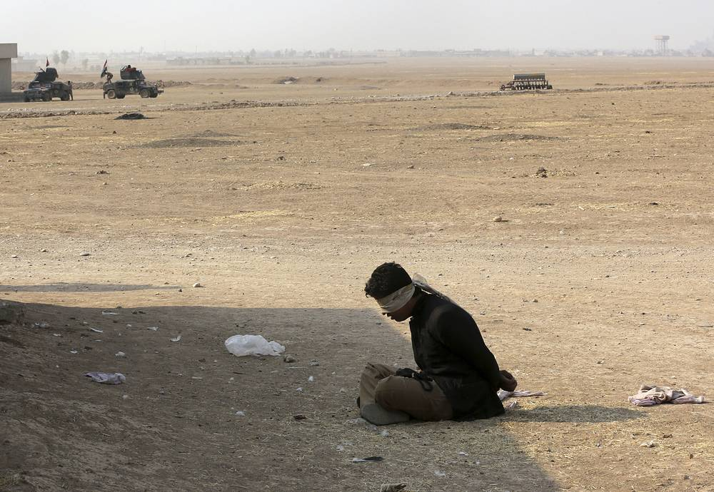A handcuffed suspected Islamic State militant sits outside his house in the village of Tob Zawa, about 9 kilometers from Mosul, Iraq, October 25