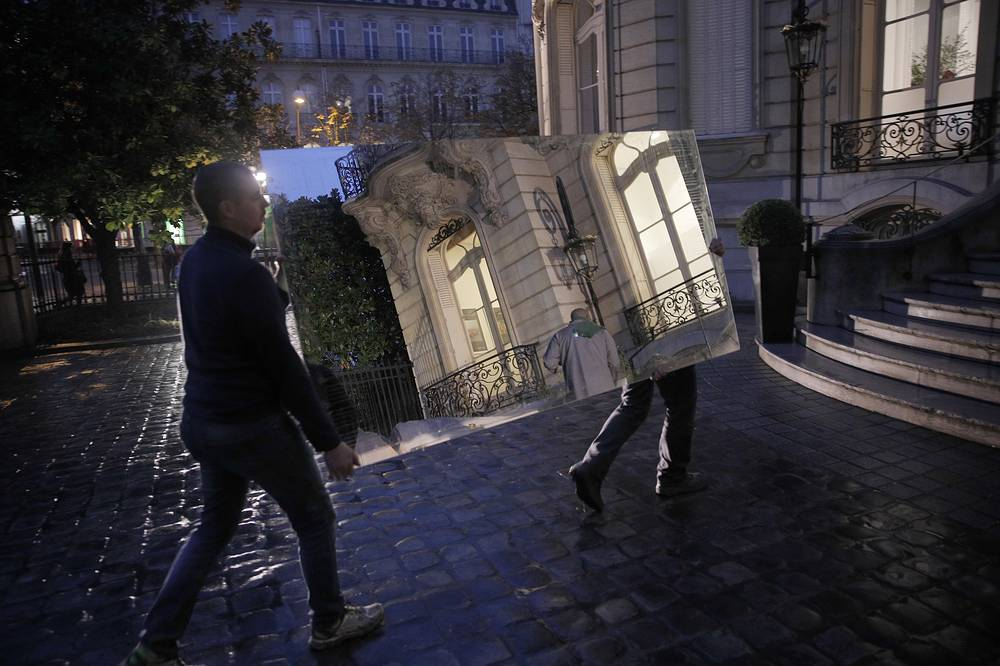 Auction house employees carry a mirror at the Artcurial auction house in Paris, November 16