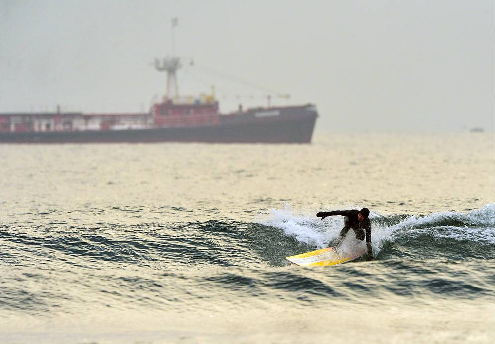 A surfer riding a wave in the Ussuri Bay, Russia, December 1