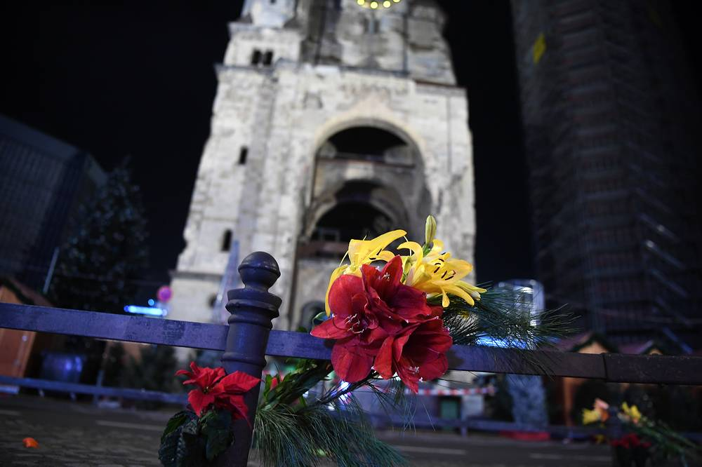 Flowers in memory of the victims placed on a railing in front of the Christmas market at the Kaiser Wilhelm Memorial Church