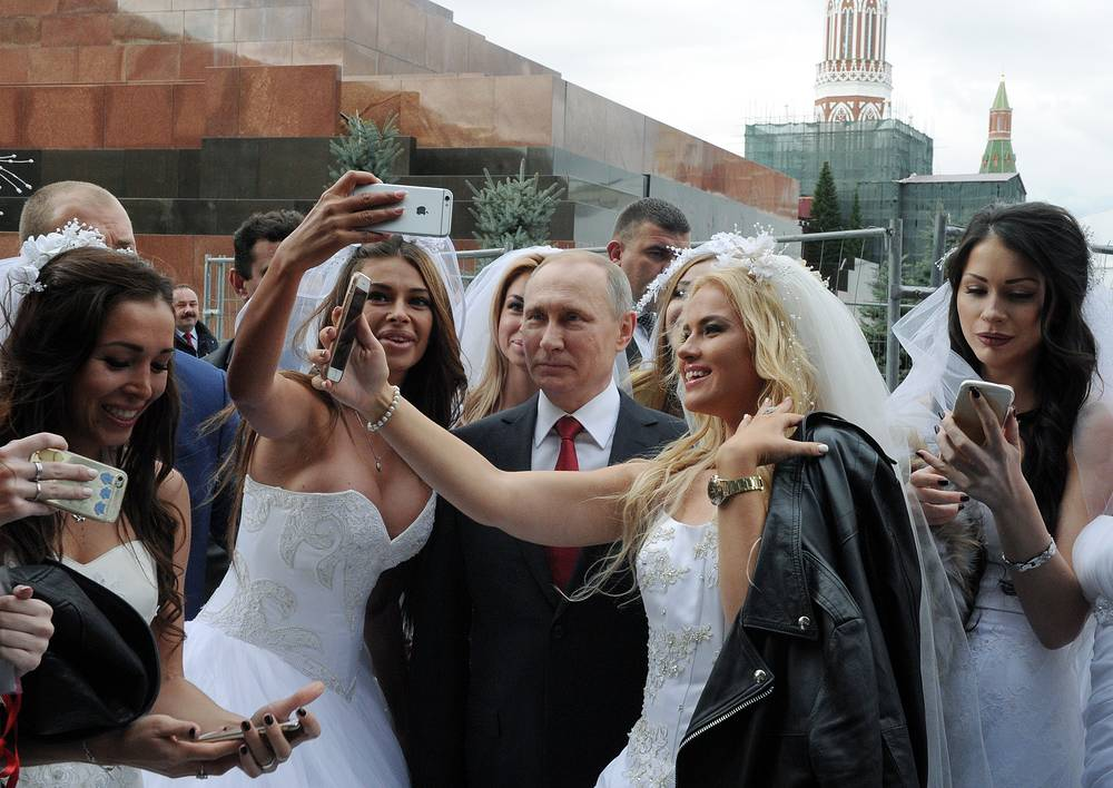 Russia's President Vladimir Putin poses for selfies with brides at the opening of Moscow City Day in the Red Square, September 10