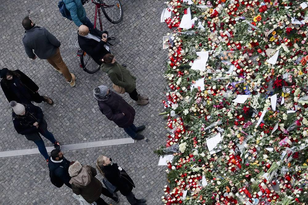 People stand near candles at the Christmas market, three days after a truck ran into the crowd and killed several people, near the Kaiser Wilhelm Memorial Church in Berlin, December 22