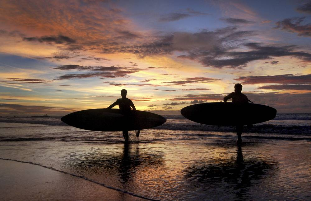 Two surfers carrying their boards at Kuta beach in Bali, Indonesia, January 18