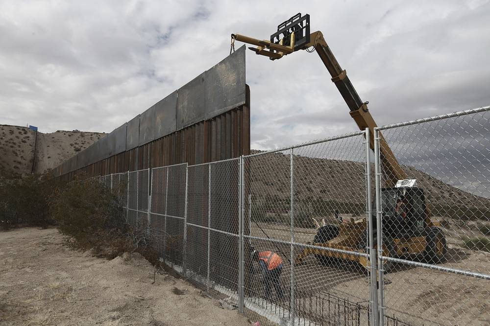 Workers raise a taller fence along the Mexico-US border between the towns of Anapra, Mexico and Sunland Park, New Mexico, USA, 2016
