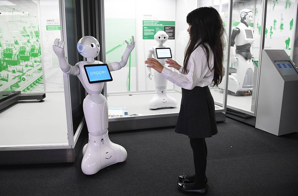 A gallery visitor interacts with 'Pepper', a French-Japanese social robot