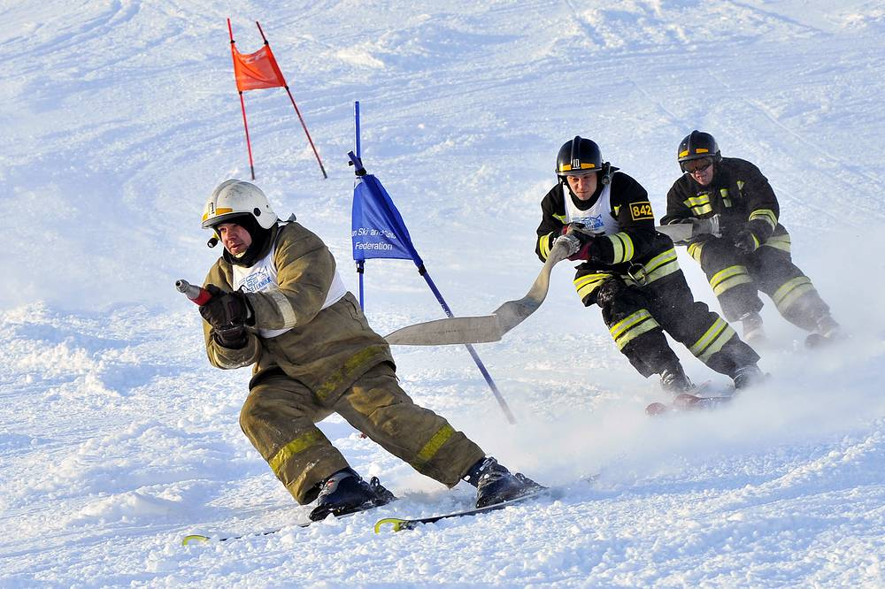 Employees of a Murmansk Region fire department in full kit hold a fire hose as they compete in an alpine skiing giant slalom event at Kikisvumchorr Alpine Ski Resort, February 25