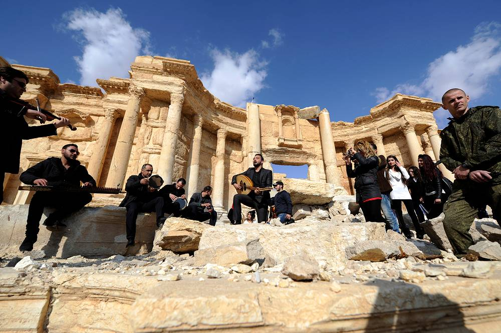 A Russian soldier stands near Syrian musicians as they play their instruments while resting on damage in the amphitheater of the historic city of Palmyra, Syria March 4