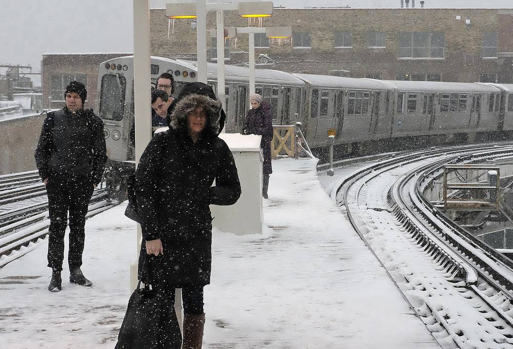 Commuters wait for the train as the snow continues fallingn in Chicago