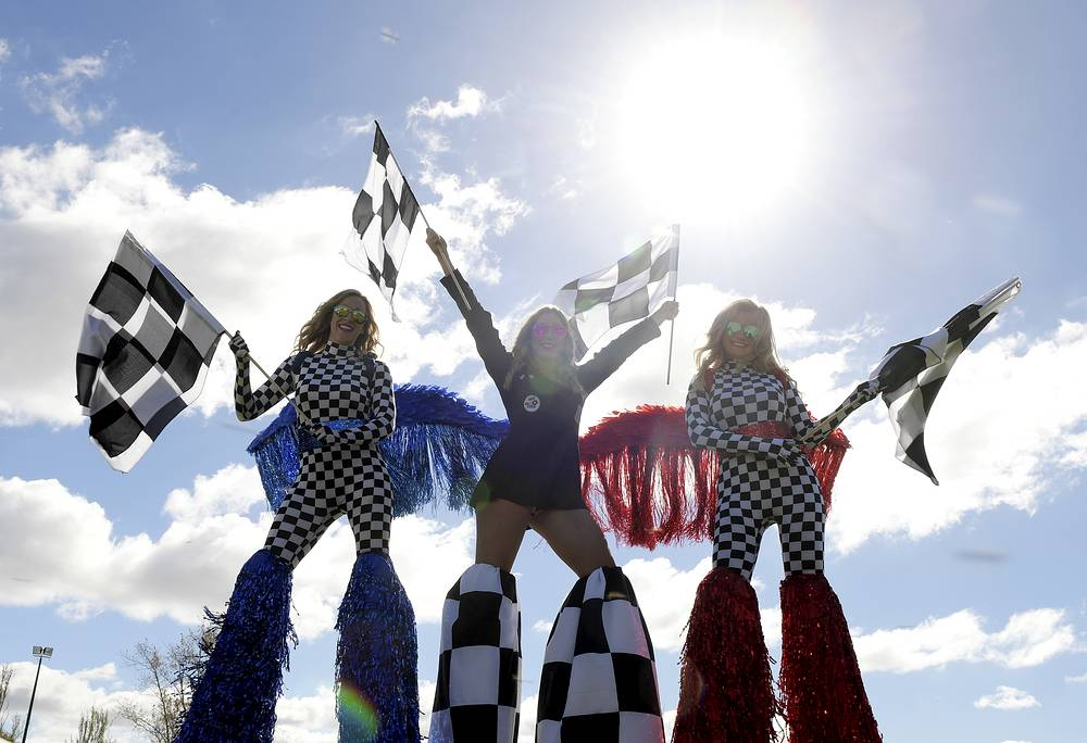 Entertainers on stilts wave flags during the qualifying sessions for the Australian Formula One Grand Prix at the Albert Park circuit in Melbourne, Australia, March 23