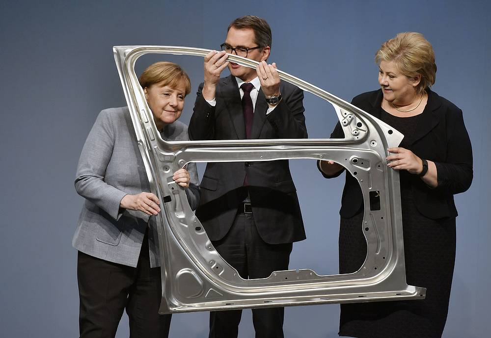 German Chancellor Angela Merkel, Hydro CEO Svein Richard Brandtzaeg and Prime Minister Erna Solberg of Norway hold a light car's door made of aluminium during the opening of a new automotive line of Norwegian aluminium producer Hydro in Grevenbroich, Germany, May 4