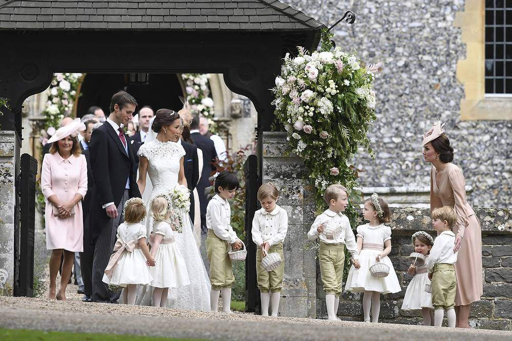 Britain's Kate, the Duchess of Cambridge stands with children, including Prince George and Princess Charlotte, following the wedding ceremony of her sister Pippa Middleton and James Matthews, at St Mark's Church in Englefield, May 20