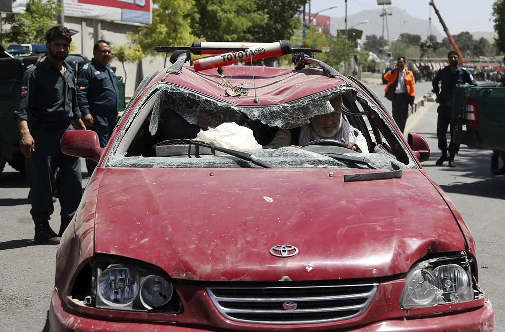 An Afghan man drives his damaged car after a suicide attack in Kabul