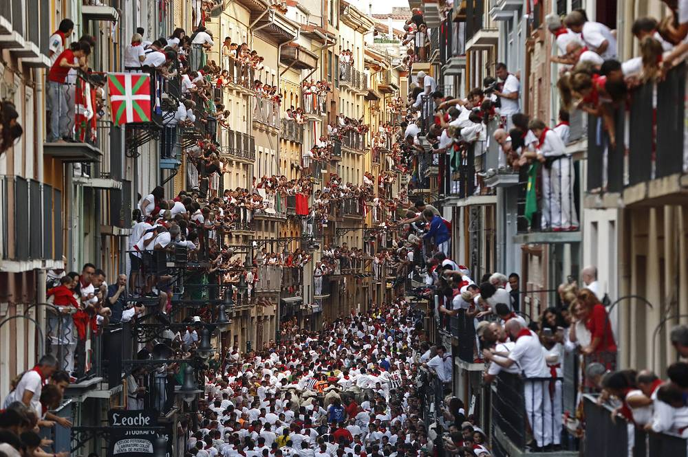 People observe from their balconies while bulls from the bull ranch Cebada Gago chase runners or 'mozos' during the first bull run of Sanfermines 2017 in Pamplona, Navarra, Spain, July 7