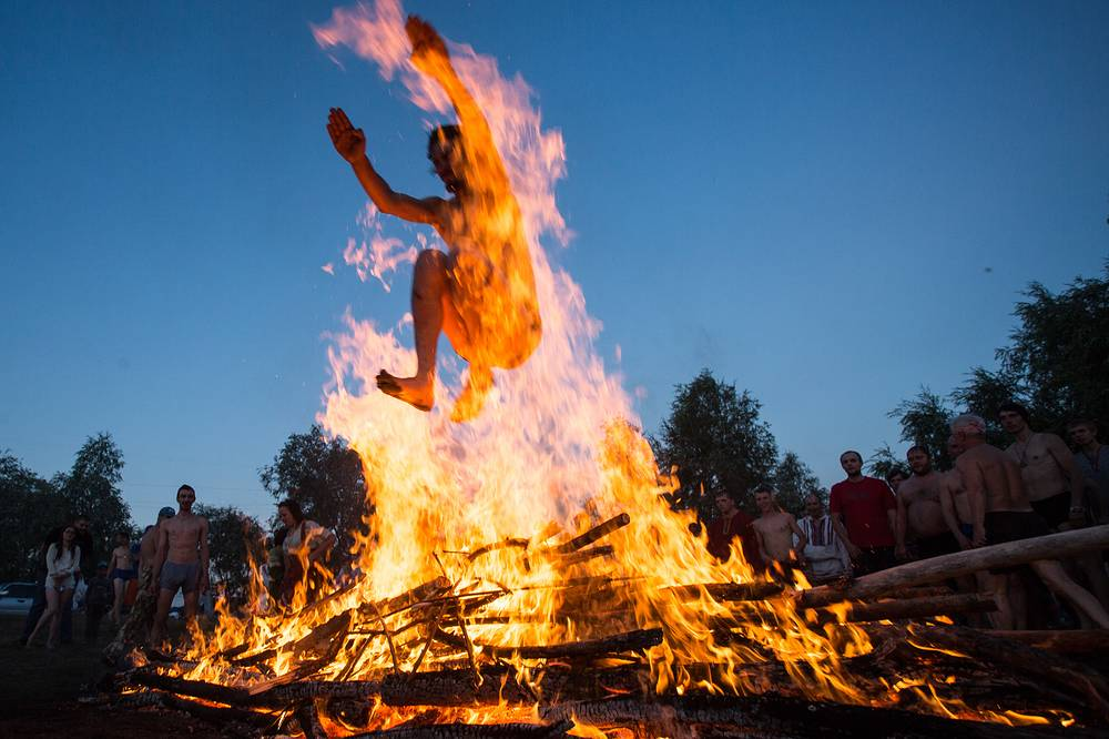 A man jumps over a bonfire during festivities marking Ivan Kupala Day, a pagan summer solstice celebration, in the village of Fadino on the Irtysh River, Russia, July 9