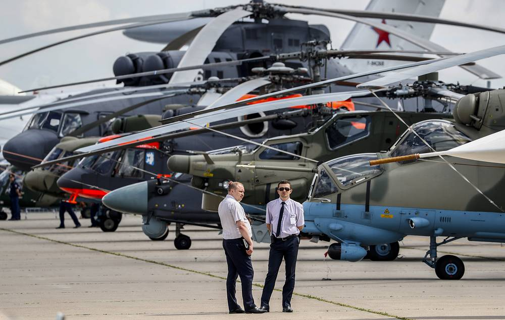 Visitors stand in front of exhibited helicopters
