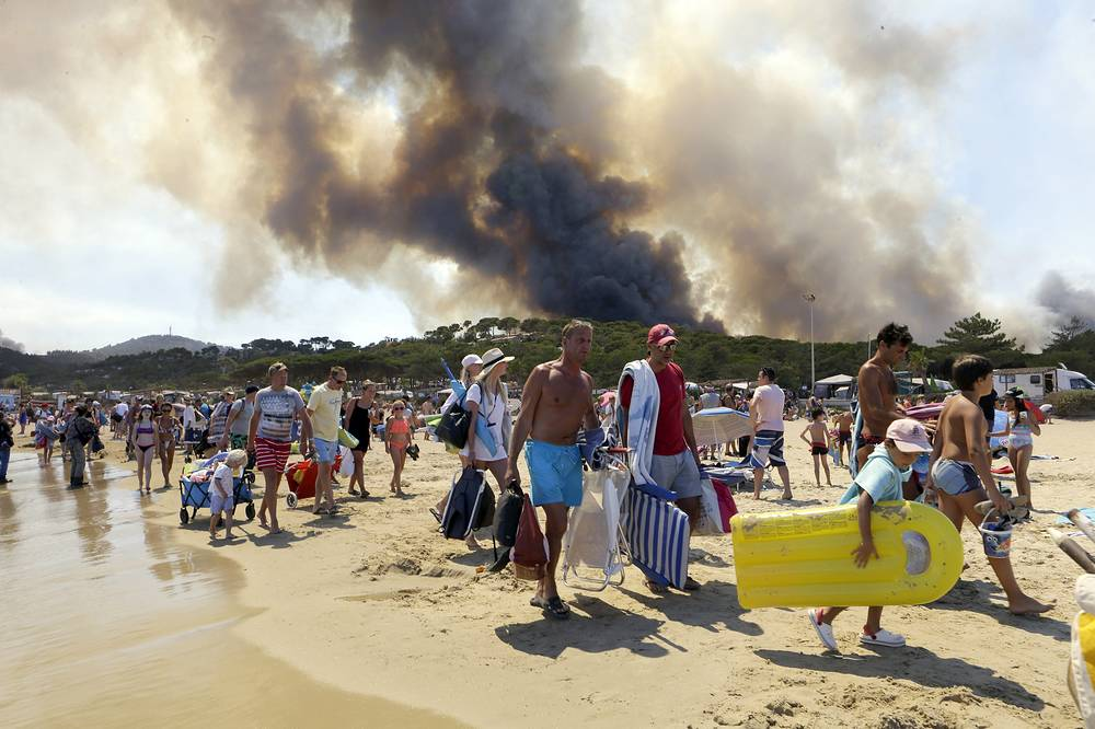 Sunbathers being evacuated from the beach in Le Lavandou, French Riviera, as plumes of smoke rise in the air from burning wildfires