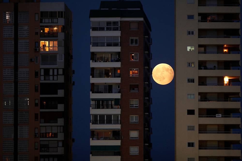 The rising moon seen during a partial lunar eclipse between buildings in Malaga, southern Spain, August 7