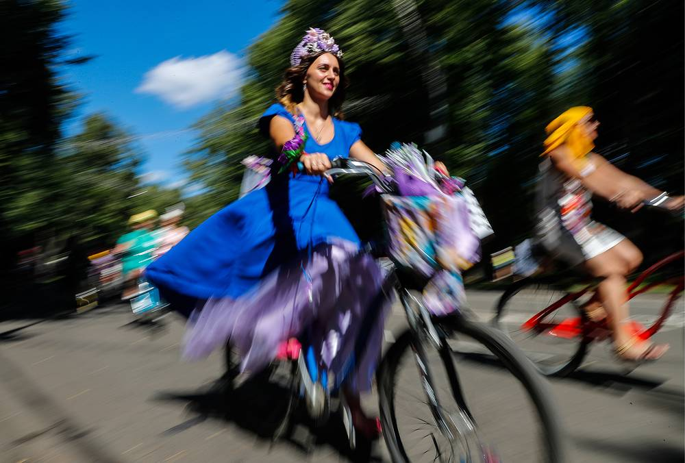 A woman wearing a dress rides a bike during a Lady on Bicycle parade in Moscow's Sokolniki Park, Russia, August 6