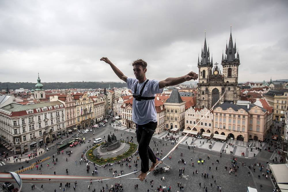 A participant balances on a slackline over the Old Town Square in Prague, Czech Republic, September 25