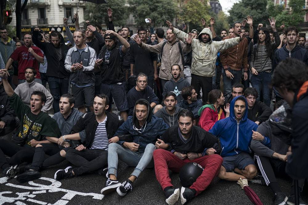People sits in the middle of the street to block Spanish riot police near a voting site in Barcelona