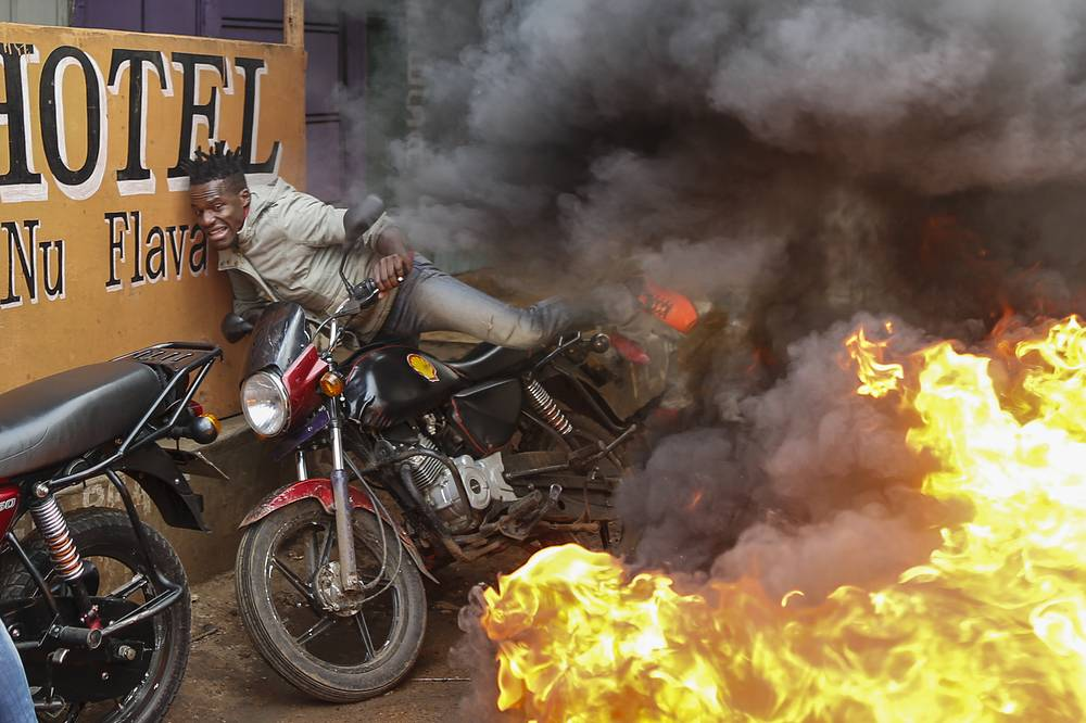 A man falls from his motorbike as he tries to pass through a burning barricade set up by supporters of the opposition coalition the National Super Alliance and its presidential candidate Raila Odinga in Kibera slum, one of the opposition strongholds in Nairobi, Kenya, October 25
