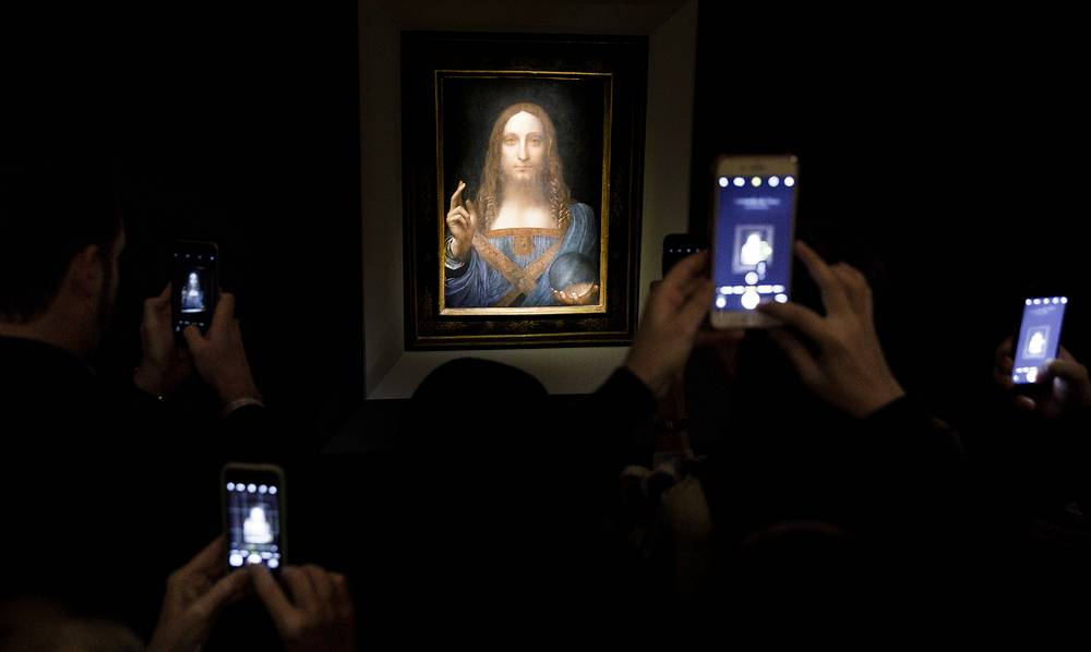 People snap pictures of the 'Salvator Mundi' painting by Leonardo da Vinci (circa 1500) during a public preview before bidding begins for the painting at Christie's auction house in New York, USA, November 15. The painting was sold for a record $450 mln