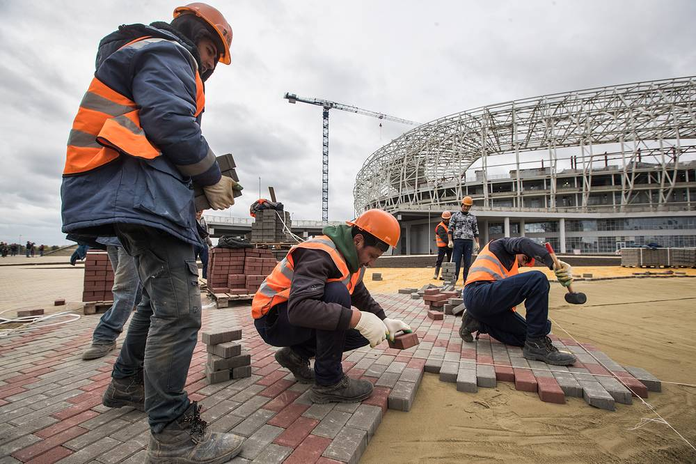 Workers lay paving slabs outside Mordovia Arena Stadium in Saransk
