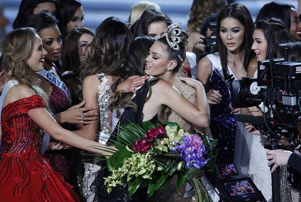 Contestants embrace new Miss Universe Miss South Africa Demi-Leigh Nel-Peters, in crown, at the Miss Universe pageant in Las Vegas, USA, November 26