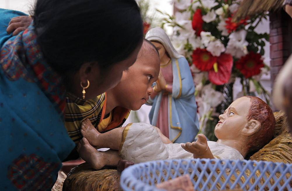 A toddler looks at an idol of young Jesus placed in a crib at Sacred Heart Cathedral on Christmas Day in New Delhi, India