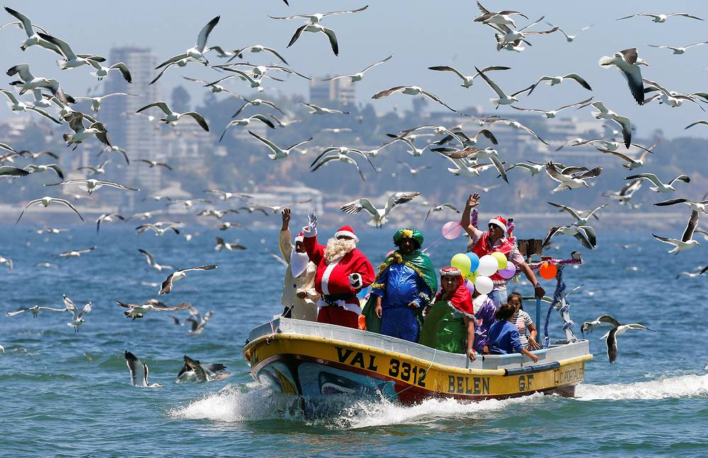 A man dressed in a Santa Claus outfit waves to people from a fisherman's boat on Christmas Eve along the coast of Valparaiso, Chile, December 24