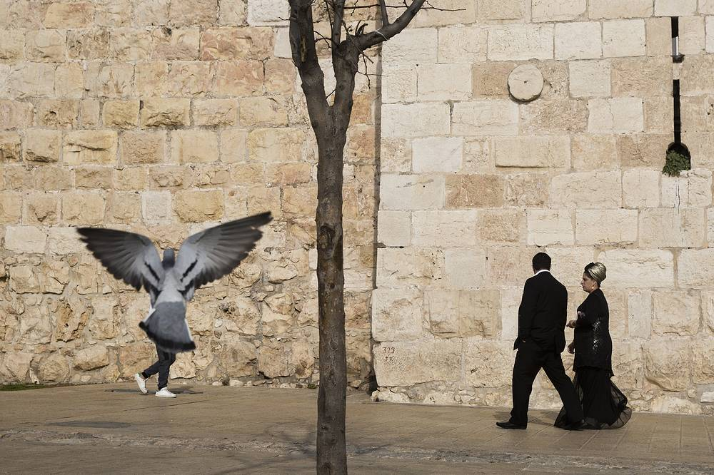 People walk along the Jerusalem's Old City walls, next to Jaffa Gate, Israel, December 23