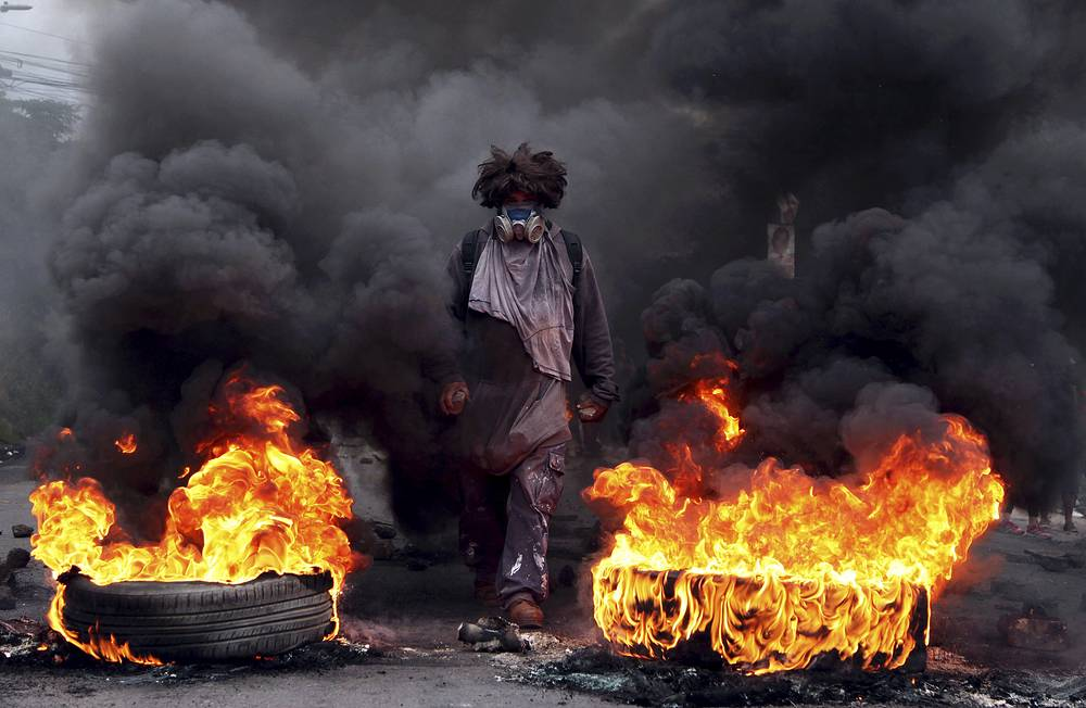 An anti-government protestors blocks a road, on the outskirts of Tegucigalpa, Honduras, December 22