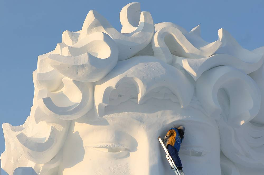 A worker carves a large snow sculpture at the Harbin International Snow Sculpture Art Expo