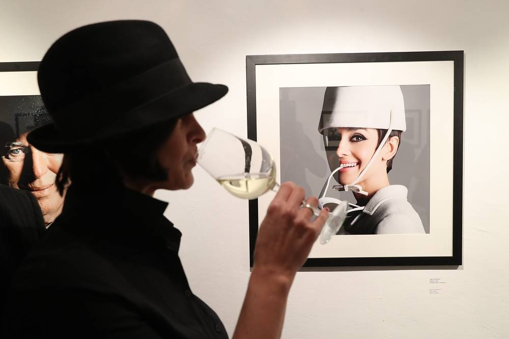 A woman drinks wine by Audrey Hepburn (Paris, 1965), a photograph by Hollywood celebrity photographer Douglas Kirkland on display at an exhibition titled Behind the Scenes, opened at the Lumiere Brothers Centre for Photograph, Moscow, Russia, January 16