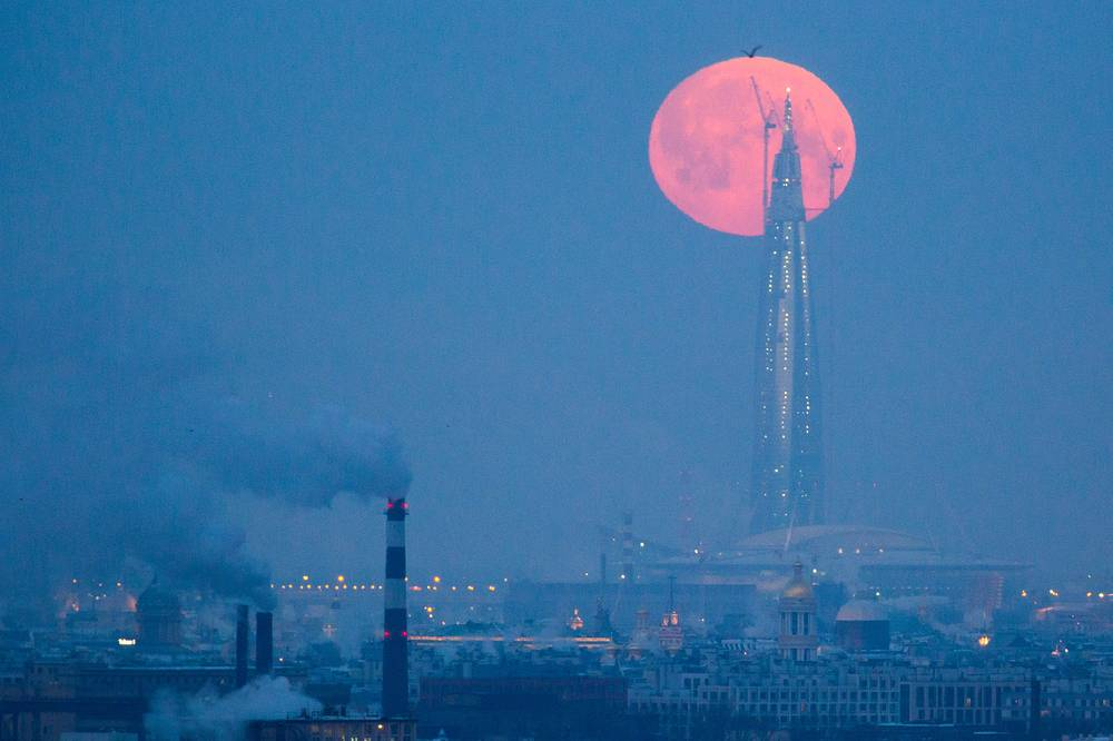 The red full moon rises over the tower of the Lakhta Center, which is under construction in Primorsky District of St Petersburg, Russia