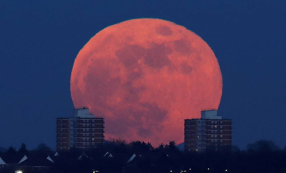 A full moon rises behind blocks of flats in north London, Britain