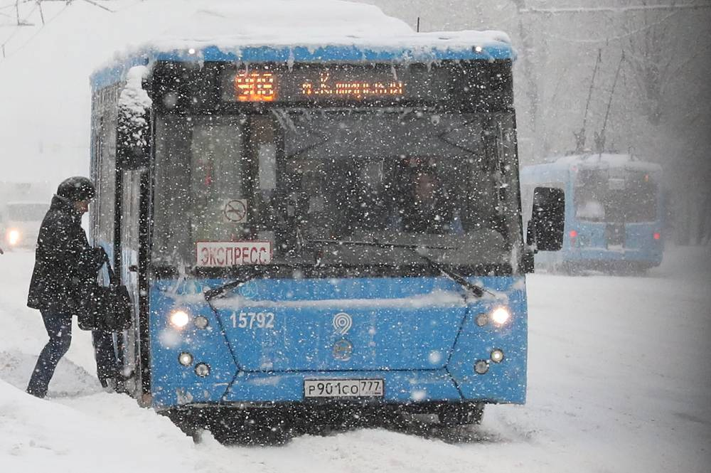 A woman getting on a bus during a snowfall in Moscow