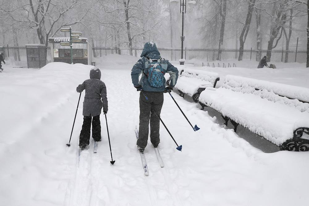 A woman with a child skiing in a park in Ostankino