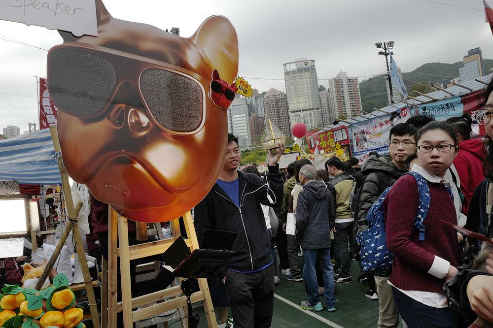 People walk past dog-themed products at a New Year market in Victoria Park, Hong Kong