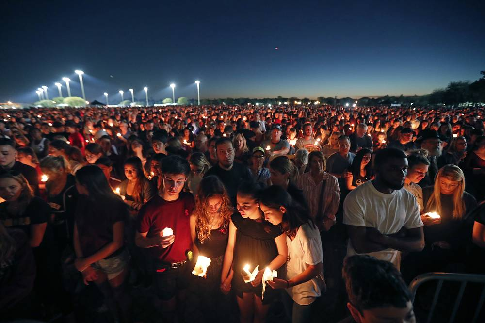 People attend a candlelight vigil for the victims of the shooting at Marjory Stoneman Douglas High School, in Parkland, USA, February 15. Nikolas Cruz, a former student, was charged with 17 counts of premeditated murder