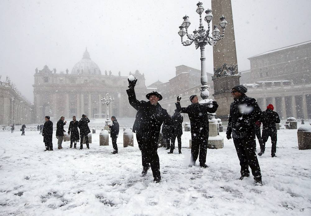 People throw snowballs as they play in a snow blanketed St. Peter's Square at the Vatican