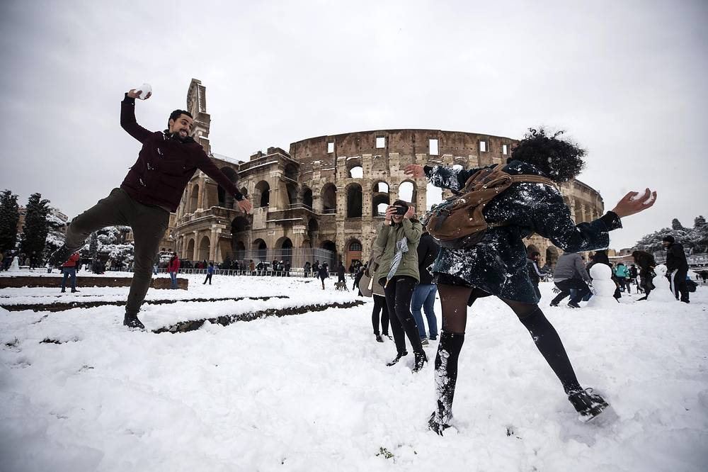 A snowball fight in progress in front of the snow-covered Colosseum in Rome, Italy, February 2