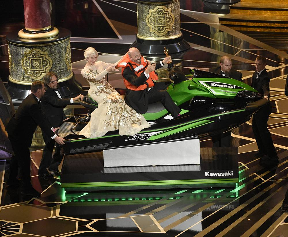 "Helen Mirren accompanies Mark Bridges, winner for the award for best costume design for ""Phantom Thread,"" as he wins a jet ski for having the shortest acceptance speech at the Oscars"