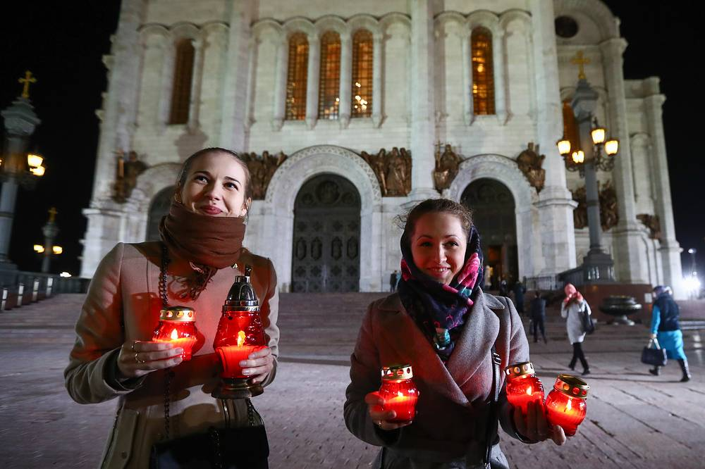 Orthodox believers hold candle lamps during an Easter service at the Cathedral of Christ the Saviour