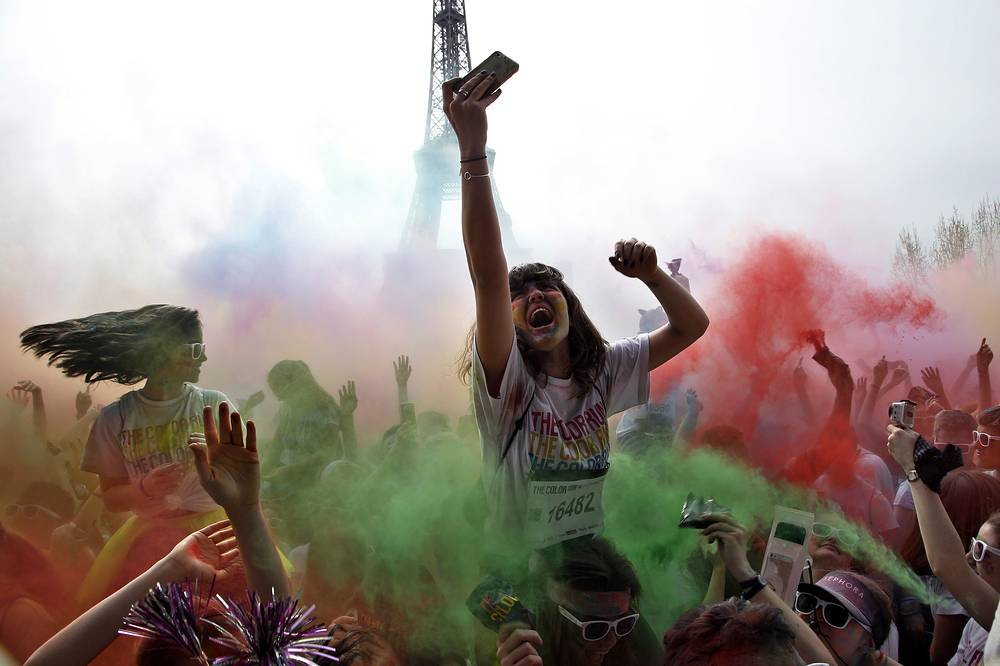 People celebrate at the end of the Color Run 2018 race, in front of the Eiffel Tower in Paris, April 15