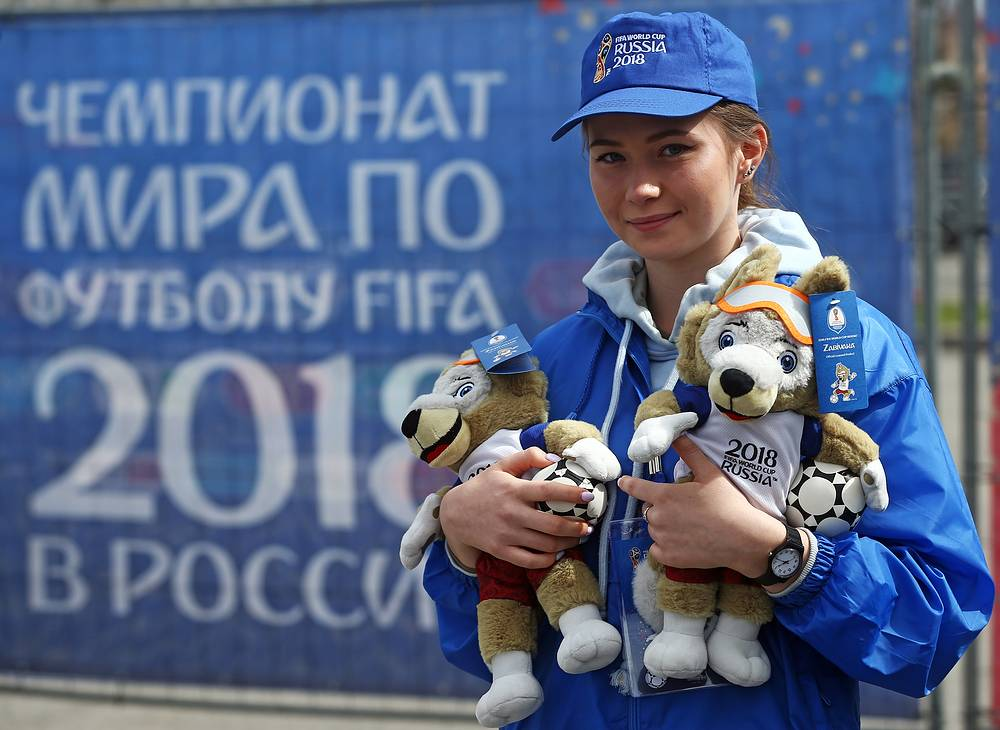 A volunteer holds stuffed toys of Wolf Zabivaka, the official mascot of the 2018 FIFA World Cup